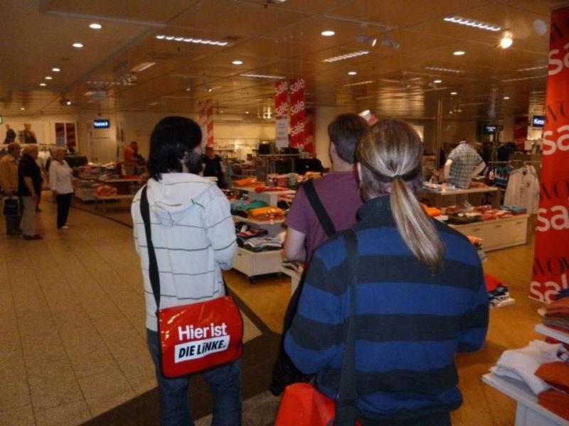 Drei Aktivisten der Partei DIE LINKE bei einer Aktion im Verkaufsraum von Karstadt in Lübeck.