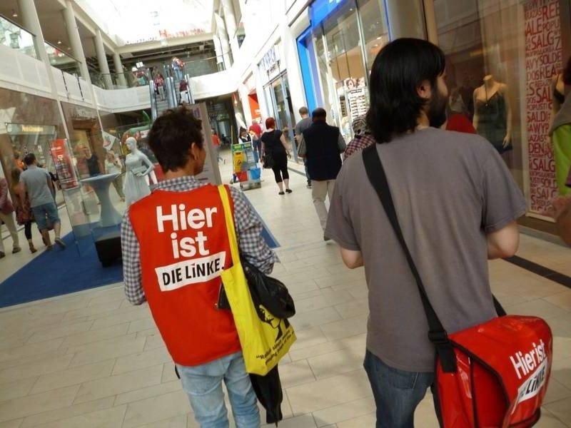 Zwei Aktivisten der Partei DIE LINKE beim Verteilen von Informationsmaterial im Sophienhof in Kiel.