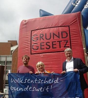"""Stefan Karstens, Anne Burmeister und Sönke Rix halten ein Transparent mit der Aufschrift """"Volksentscheid - bundesweit!"""""""