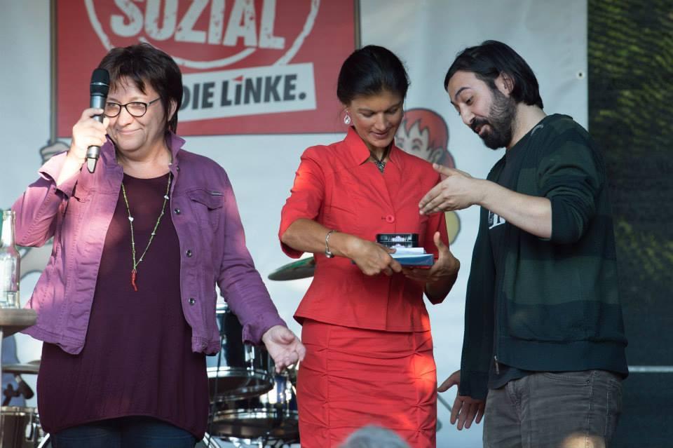 Marcel Mansouri überreicht Sahra Wagenknecht eine Packung Kieler Sprotten.