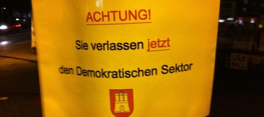 """Selbstgemachtes Schild mit der Aufschrift: """"Achtung! Sie verlassen jetzt den demokratischen Sektor!"""" mit Hamburger Wappen (Quelle: onlineaktivisten.de)"""
