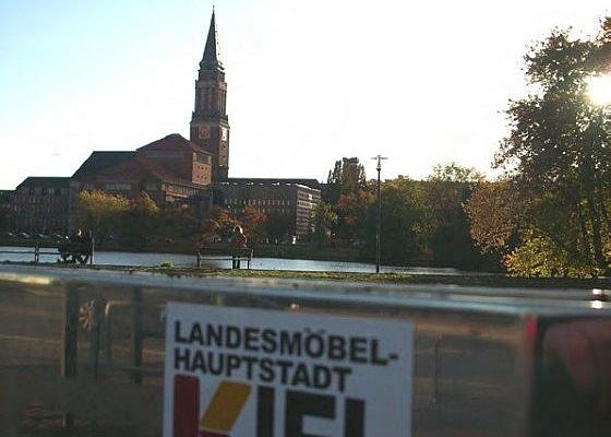 """Aufkleber an Sitzbank mit der Aufschrift: """"Landesmöbelhauptstadt Kiel"""", im Hintergrund das Kieler Rathaus. (planten.de CC BY-NC-SA 2.0)"""