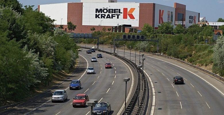 Foto einer riesigen Möbel Kraft-Filiale, im Vordergrund eine Autobahn (Steffen Zahn@flickr.com CC BY 2.0)