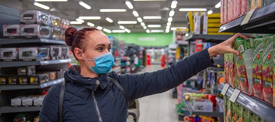 Eine Frau mit Einwegmaske greift in einem Supermarkt in ein Regal.