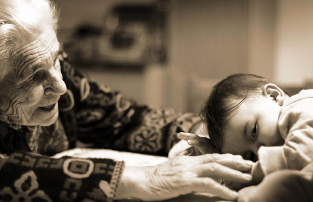Eine alte Frau und ein Baby sitzen sich gegenüber. Die alte Frau streckt ihre Arme in Richtung des Baby aus.