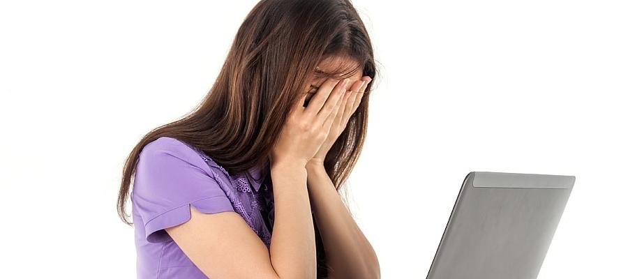 Frau sitz vor einem Laptop und schlägt die Hände vor das Gesicht.