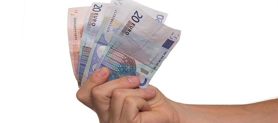 Hand, die zwei 20-Euro-Scheine und einen 10-Euro-Schein hält.