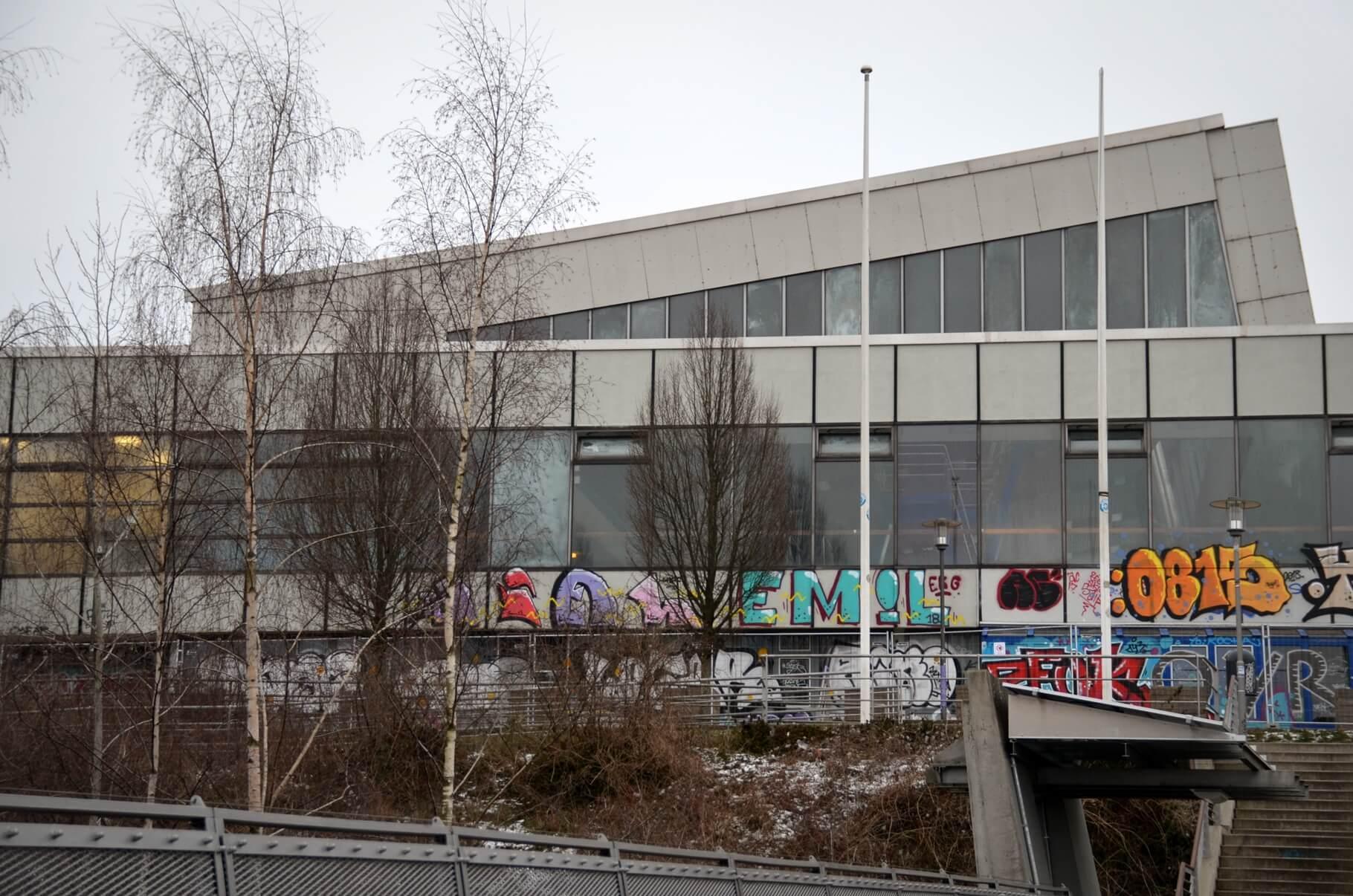 Schwimmhalle in Kiel-Gaarden mit Graffiti, davor ein Bauzaun.