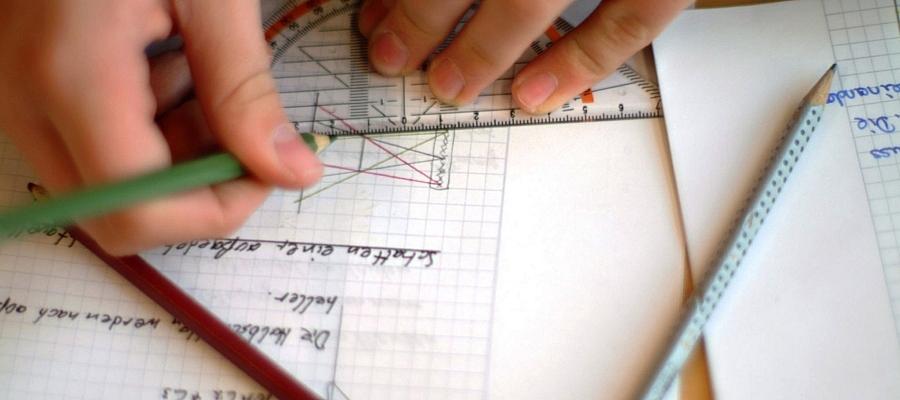 Zwei Hände, die mit einem Buntstift und einem Geodreieck Linien auf ein karriertes Blatt mit mathematischen Formeln zeichen.