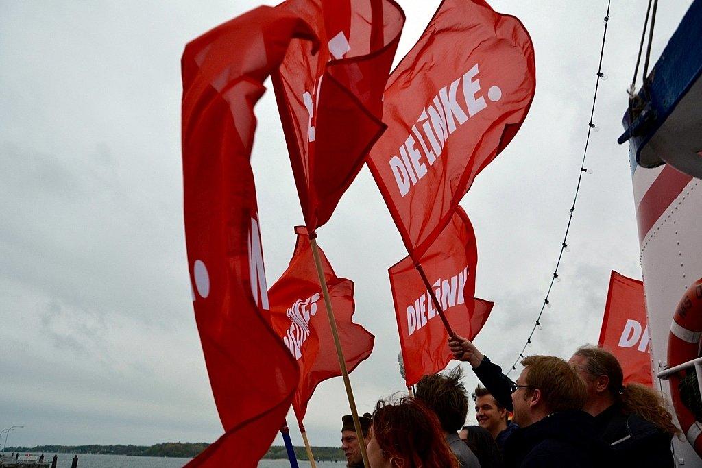 """Eine Gruppe von Personen an Bord eines Schiffes hält mehrere rote Fahnen mit Aufschrift """"DIE LINKE"""" in den Wind."""
