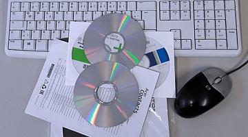 Eine Tastatur, ein Stapel mit CD-ROMs und eine Computer-Maus.