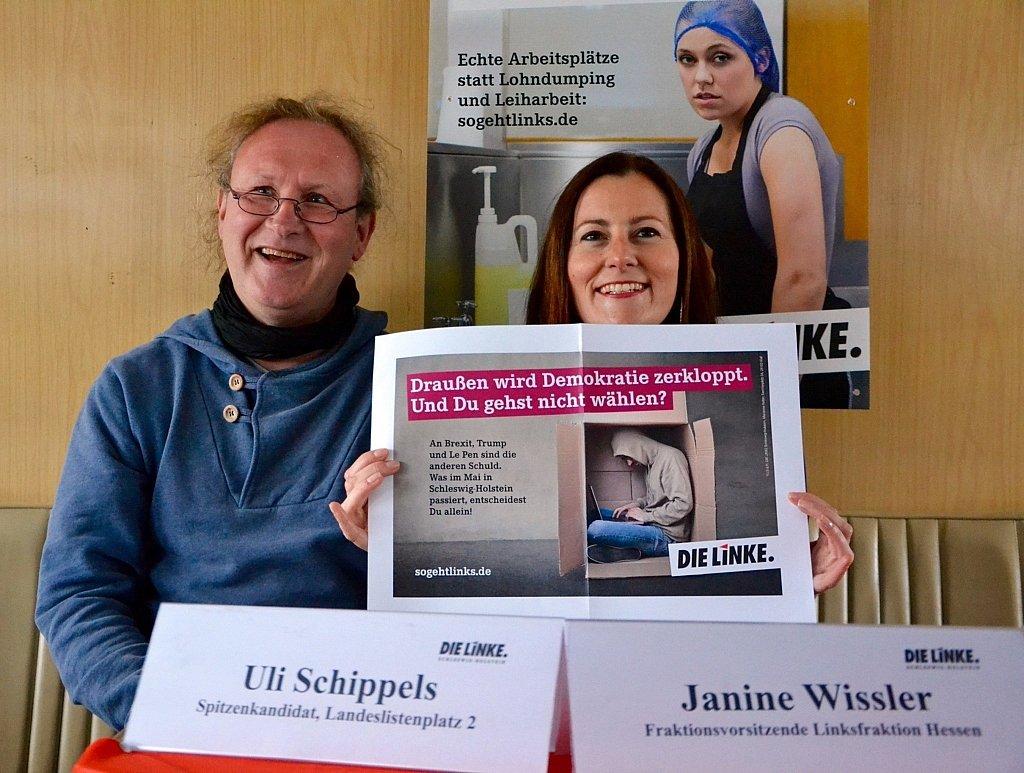 """Uli Schippels und Janine Wissler (beide DIE LINKE) halten ein Poster mit folgender Aufschrift hoch: """"Draußen wird die Demokratie zerkloppt. Und Du gehst nicht wählen? An Brexit, Trump, und Le Pen sind die anderen Schuld. Was im Mai in Schleswig-Holstein passiert, entscheidest Du allein!"""""""