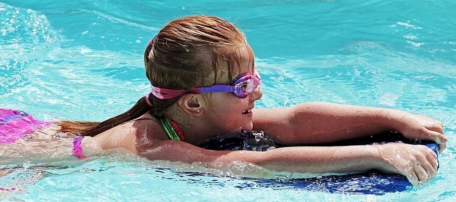 Junges Mädchen mit Schwimmbrille und Schwimmbrett, im Wasser.
