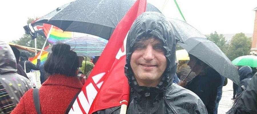 """Stefan Karstens (DIE LINKE) in Regenjacke trägt eine rote Fahne mit Aufschrift """"DIE LINKE"""", im Hintergrund sind zahlreiche Menschen bei einer Demonstration zu sehen. Es regnet sehr stark."""