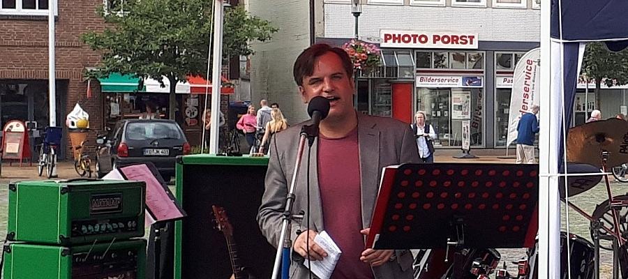 Stefan Karstens (DIE LINKE) steht an einem Mikrofon und hält auf dem Schiffbrückenplatz in Rendsburg eine Rede.