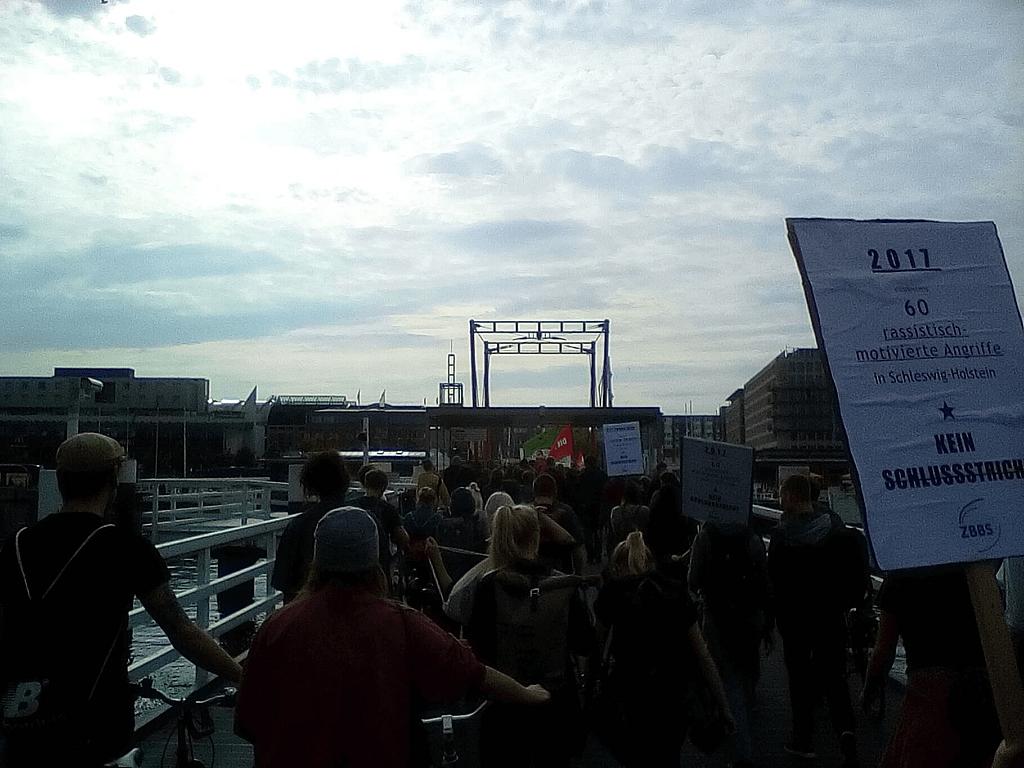 Ein Demonstrationszug in Kiel, der über die Hörnbrücke geht. Im Vordergrund ein Schild mit der Aufschrift: 2017 - 60 rassistisch motivierte Angriffe in Schleswig-Holstein. Kein Schlussstrich!