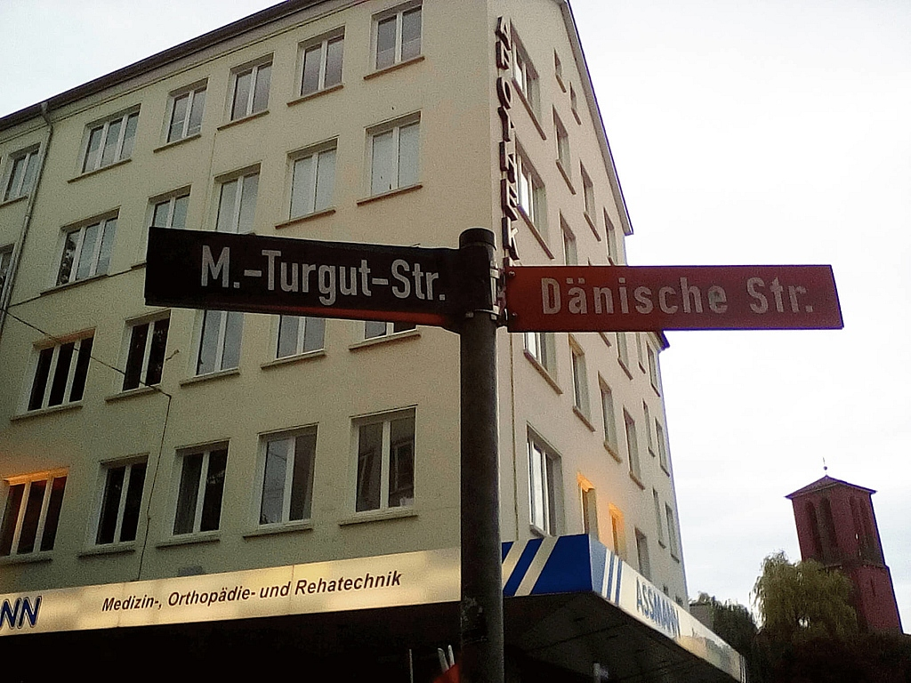 Ein Schild mit Straßennamen: M.-Turgut-Straße = Dänische Straße.