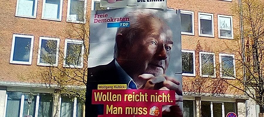 """Es hängen zwei Wahlplakte übereinander an einem Laternenmast: Oben ein Plakat der Partei DIE LINKE mit dem Slogan """"Kita nur mit Kohle?"""", unten ein größeres Plakat der FDP. Auf dem Plakat der FDP ist Wolfgang Kubicki zu sehen, darunter der Slogan """"Wollen reicht nicht. Man muss auch können."""""""