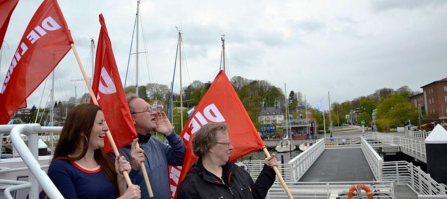 """Janine Wissler, Uli Schippels und Marianne Kolter (alle DIE LINKE) an Bord eines Schiffes, welches an der Reventlou-Brücke in Kiel angelegt hat. Alle halten eine rote Fahne mit Aufschrift """"DIE LINKE"""" in der Hand."""